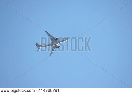 Airplane Flying In The Clear Blue Sky, Bottom View. Commercial Plane Taking Off And Gaining Altitude