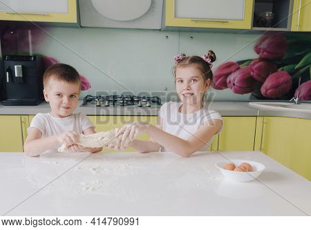 Beautiful Boy And Girl Stretch Dough In The Kitchen Mess Around And Have Fun While Cooking