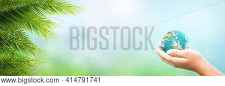 Human Hand Holding Global Over Blurred Blue And Green Nature Background. Elements Of This Image Furn
