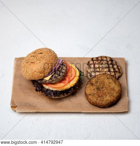 Grilled Double Or Triple Meat Burger With Tomatoes, Onion And Lettuce On Parchment Paper. Set Of Ing