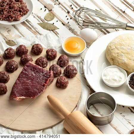 Raw Meat Ball, Beef Filling For Dumplings Or Raw Dough Ravioli On White Wooden Table. Ingredients An