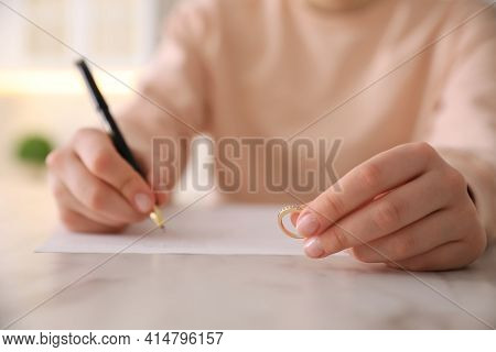 Woman With Wedding Ring Signing Divorce Papers At Table Indoors, Closeup