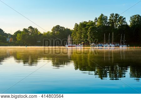 Calm Morning Lake Surface With Sailing Boats And Trees On Horizon And Reflection Of It. Serene Scene