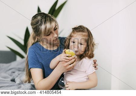 Mom Helps A Sick Daughter To Use A Nebulizer, Hugging Her At Home On The Couch, Mom Helps To Inhale