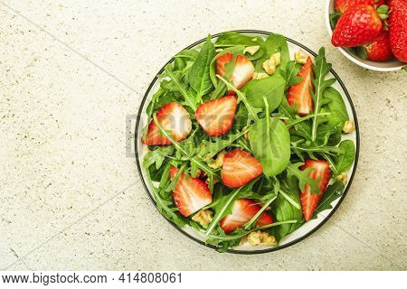 Summer Strawberry Salad. Spinach Leaves, Arugula, Walnuts On Gray Background. Healthy Food Concept.