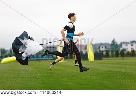 Junior Football Player Running With Parachute. Soccer Endurance And Strength Training. Player Speed