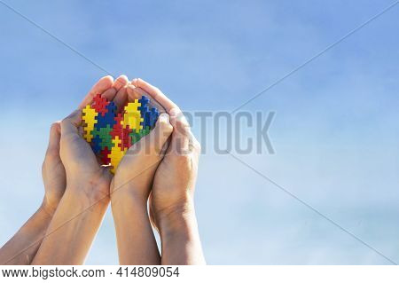 Autistic Kid Hands With Multicolored Puzzle Heart Supported By Mother Hands Over Blue Sky Background