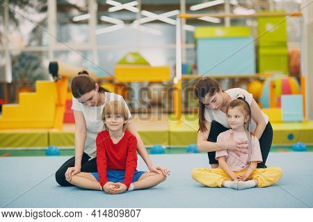Kids Doing Stretching Exercises In Gym At Kindergarten Or Elementary School. Children Sport And Fitn