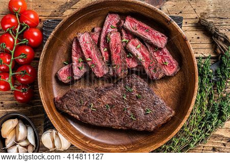 Grilled Sliced Top Blade Or Denver Beef Meat Steak In A Wooden Plate With Herbs. Wooden Background.
