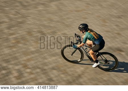 High Angle View Shot Of Professional Female Cyclist In Cycling Garment And Protective Gear Looking F