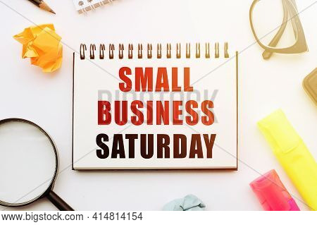 Text Small Business Saturday In Notebook On White Table With Office Tools.