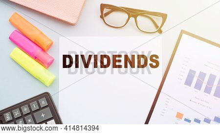 The Text Dividends On Office Desk With Calculator, Markers, Glasses And Financial Charts.