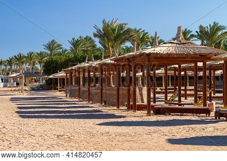 On A Deserted Empty Beach Sun Loungers And Umbrellas On The Shores Of The Red Sea, Evening, Winter S