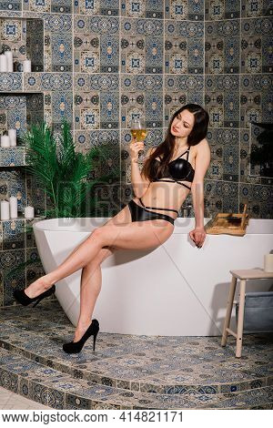 Beautiful Girl In Underwear In The Bathroom Sitting On A Luxurious White Bath