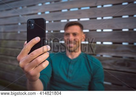Young Happy Attractive Man Using Smartphone Outdoors At Sunset. Man Holding Modern Black Mobile Phon