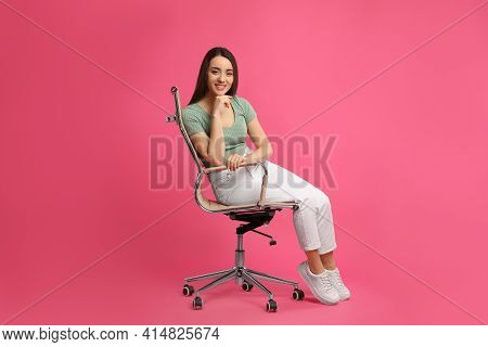 Young Woman Sitting In Comfortable Office Chair On Pink Background