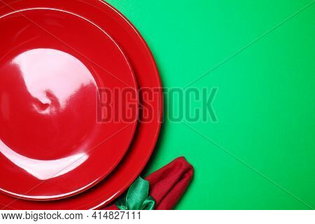 Set Of Ceramic Dishware On Green Background, Flat Lay. Space For Text