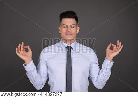 Businessman Meditating On Dark Grey Background. Personality Concept
