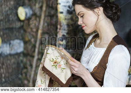 Portrait Of Young Smiling Caucasian Brunette Woman Posing With Fancywork Hoop In Retro Dress In Rura