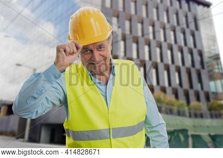 Old Constructor Man In Work Attire Vest And Yellow Helmet Making Respectful Greeting Gesture Touchin