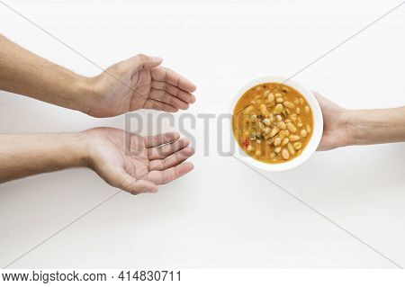 Hand Giving Soup Bowl Needy Person. High Quality And Resolution Beautiful Photo Concept