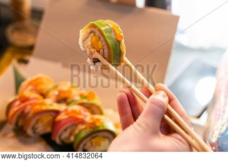 Close Up Of Chopsticks Taking Portion Of Sushi Roll On The Table Restaurant. Eating Sushi Roll Using