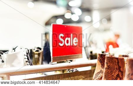 Red Bright Sale Sign In A Womenswear Store, Surrounded By Shoes And Accessories. Seasonal Discount O