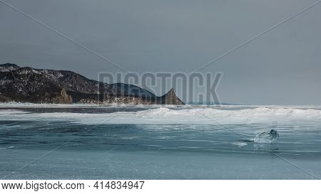 On The Smooth Surface Of The Frozen Lake Lies A Bizarre Shiny Shard Of Ice And Snowdrifts. Against T