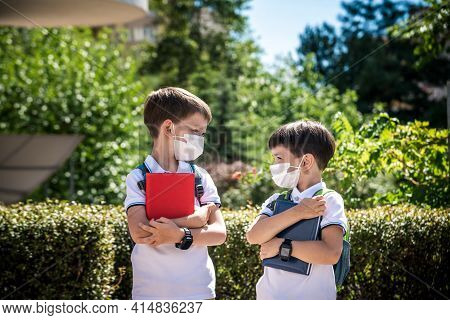 Two Boys, Schoolchildren In Black School Uniforms With Backpacks In A Medical Mask Go To School Inde