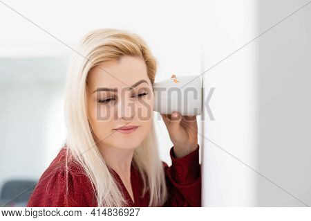 Beautiful Young Woman Eavesdropping Near The Wall Using Tea Cup.