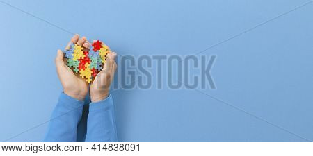 World Autism Awareness Day Concept. Child Hand Holding Colorful Puzzle Heart On Light Blue Backgroun