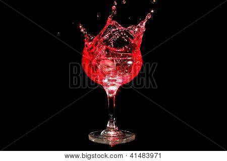 Ice cube splashing in a glass of wine
