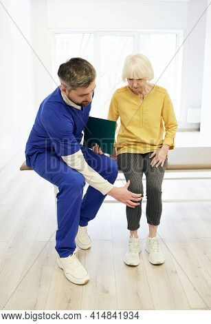 Physiotherapist Examining Patients Knee. Senior Patient With Knee Injury Visit Her Physiotherapist