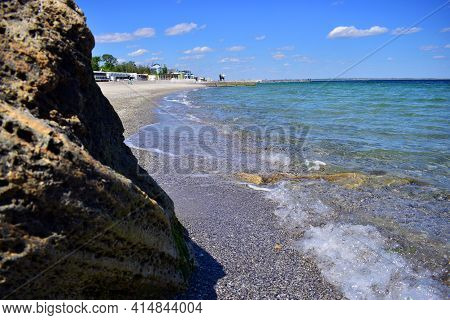 A Picturesque Seascape Overlooking The Blue Sea, Stones, Bright Sunny Day. The Waves Break Against T