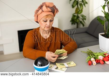Female Psychic Or Fortune Teller Gesturing With Her Hands Indicating Money