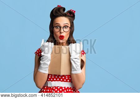 Surprised Pin Up Woman In Polka Dot Dress And Glasses Holding Book Over Blue Studio Background, Copy