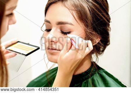 Eyelash Extension Procedures. Beautiful Young Caucasian Woman Receiving Eyelash Extension By Master