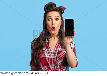 Shocked Pin Up Woman Showing Smartphone With Blank Screen On Blue Background, Mockup For Your App Or