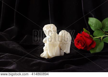 A Little Angel With Wings And A Red Rose On A Black Background. Funeral Concept, Condolences