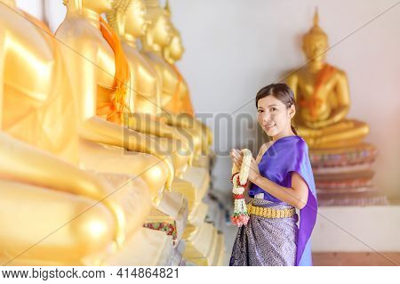 Attractive Thai Woman In An Ancient Thai Dress Holds A Garland Of Fresh Flowers Paying Homage To Bud