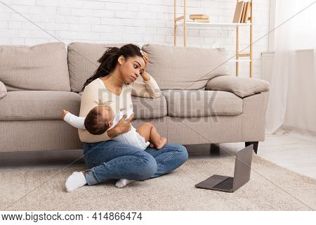Exhausted Black Mother Holding Crying Baby Sitting At Laptop Indoor