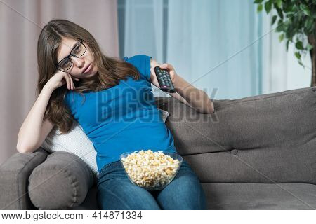 Bored Girl In Glasses, Young Tired Woman With Boring Face Is Sitting On Couch Or Sofa At Home In Liv