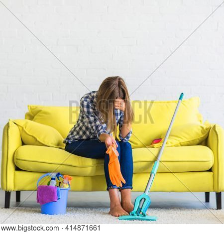 Frustrated Young Woman Sitting Sofa With Cleaning Equipments. High Quality And Resolution Beautiful