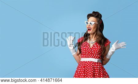 Unbelievable News. Excited Pin Up Woman In Cool Retro Dress Expressing Her Shock On Blue Background,