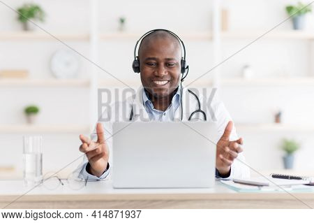Highly Qualified African American Doctor Consultating Patients Distantly Using Laptop Computer And E