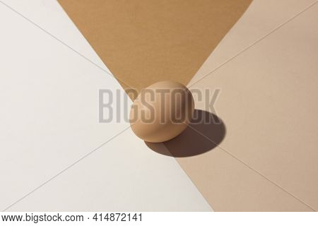 Easter Holiday Card Minimalism. One Beige Chicken Egg Lies On Three Shades Of Beige Pastels With A H