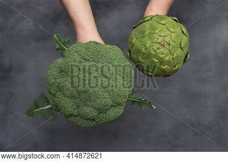 Caucasian Male Hands Holding Brocoli And Artichoke Isolated On Gray Background.