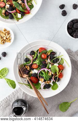Top Down View Of Blackberry Spinach Salads Surrounded By Blackberries, Walnuts And Balsamic Vinaigre