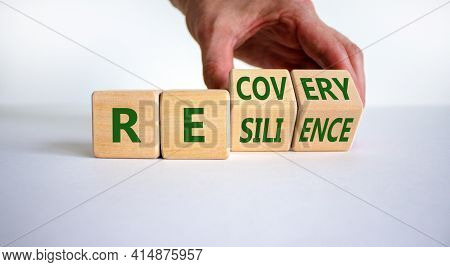 Recovery And Resilience Symbol. Businessman Turns Cubes And Changes The Word 'recovery' To 'resilien