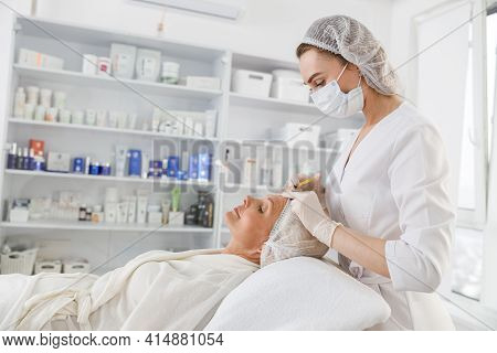 Beautician Makes Mesotherapy Injections To A Senior Woman. Treatment Of A Woman By A Beautician For